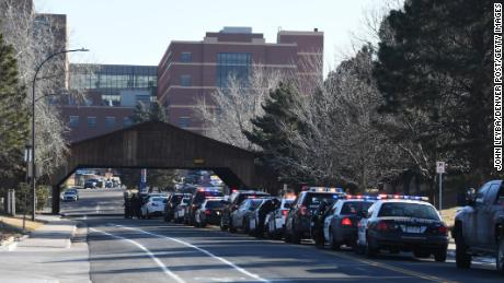 Officers from various police agencies line up in front of a Littleton hospital as they wait for a procession for a fallen deputy.