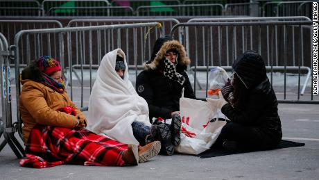 Revellers stay warm in Times Square early Sunday morning as they prepare for New Year's Eve celebrations.
