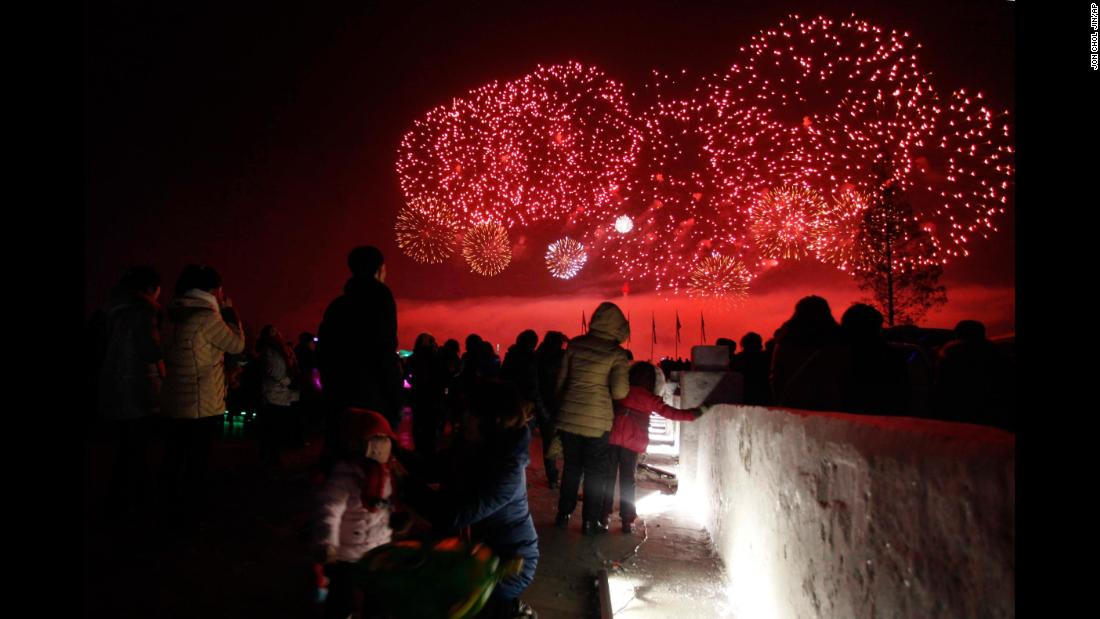 People in Kim Il Sung Square watch fireworks light the sky above the Taedong River in Pyongyang, North Korea.