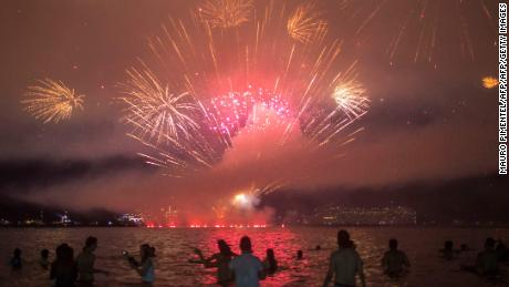 TOPSHOT - People watch fireworks during New Year's celebrations at Copacabana beach in Rio de Janeiro on January 1, 2018.  / AFP PHOTO / MAURO PIMENTELMAURO PIMENTEL/AFP/Getty Images