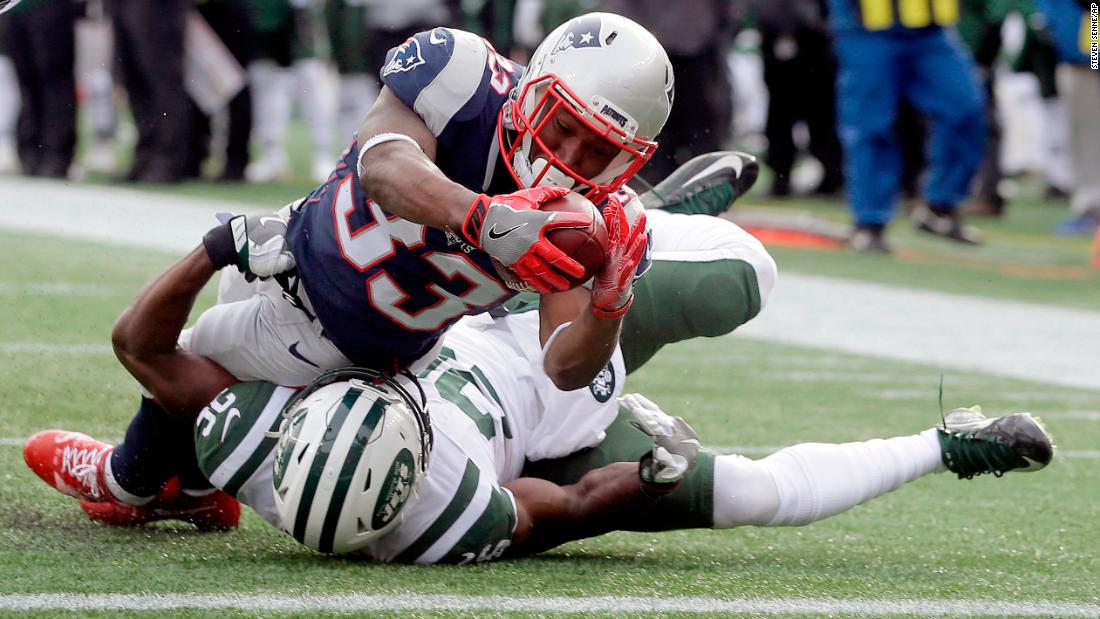 New England running back Dion Lewis dives over New York Jets safety Marcus Maye to score a touchdown on Sunday, December 31. New England won 26-6 to clinch home-field advantage in the AFC playoffs.