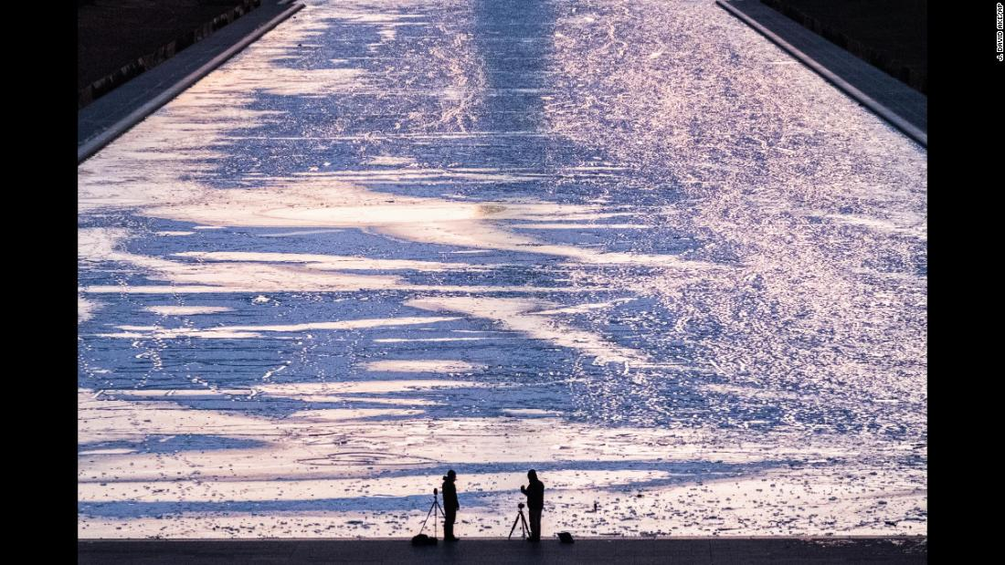 Two photographers are silhouetted against the frozen surface of the Reflecting Pool in Washington as they capture the first sunrise of the new year.