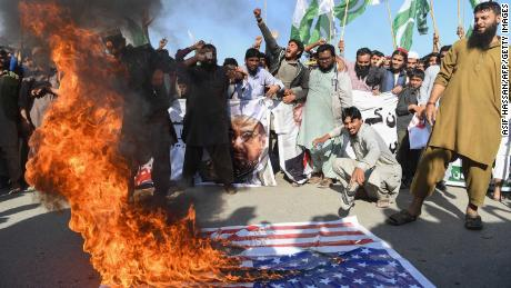 Activists burn the American flag at a protest in Karachi on Tuesday