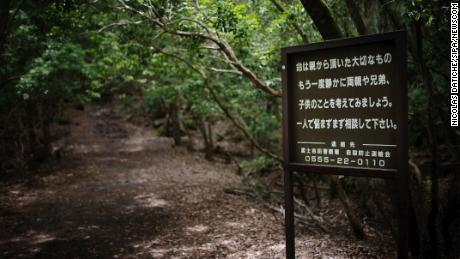 A sign at the entrance of the Aokigahara forest urges suicidal visitors to reach out for help.