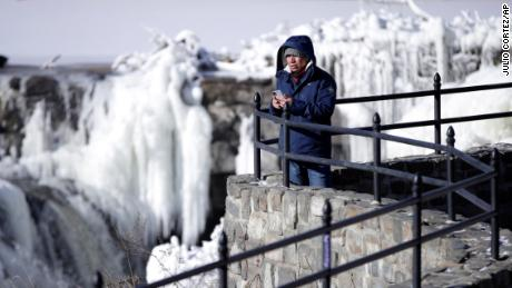 Obdulio Arenas looks over the partially frozen falls at the Paterson Great Falls National Historical Park, Tuesday, Jan. 2, 2018, in Paterson, N.J. The Northern New Jersey region continued to experienced deep cold weather to start the new year. (AP Photo/Julio Cortez)
