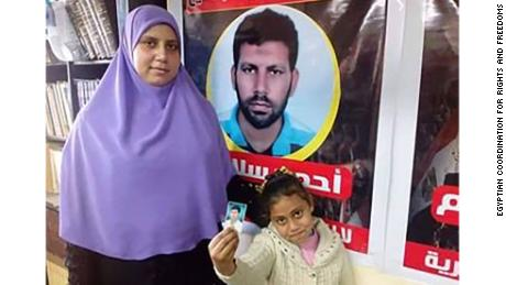 Ahmed Salama's wife and daughter are pictured in an undated image in Cairo. They are standing in front of a sign with Salama's image. Salama was  executed this week.