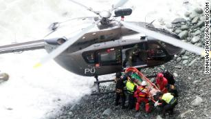 Rescue personnel transfer an injured person to a helicopter after the accident.