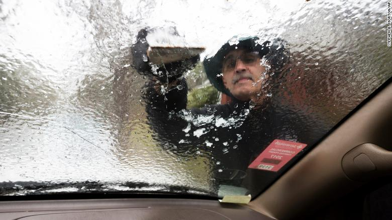 Omar Elkhalidi scrapes ice off his windshield in Savannah, Georgia, on Wednesday, January 3. Only a few motorists ventured out in freezing rain that coated bridges and ramps with ice, forcing police to close roads and highways.