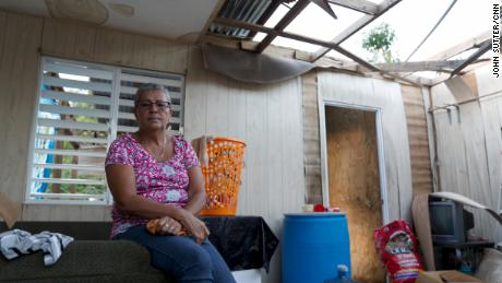 Carmen Torres lives with her sister across the street from her tattered home.