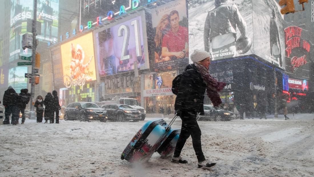 Rebecca Hollis drags her suitcases through New York's Times Square on January 4