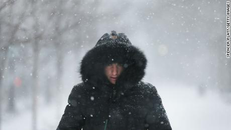 A man walks through the streets of Boston as the snow begins to fall from a massive winter storm on January 4 in Boston, Massachusetts. Schools and businesses throughout the Boston area are closed as the city is expecting over a foot of snow and blizzard like conditions throughout the day.