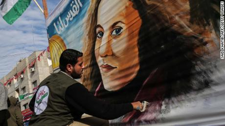 A Palestinian artist paints a portrait of Ahed Tamimi in Gaza on Wednesday.