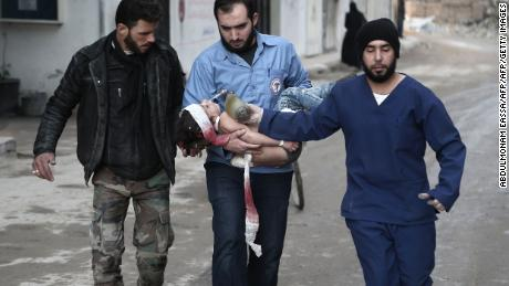 Rescuers from the volunteer White Helmets rescue group with a girl they pulled from the rubble following airstrikes in Eastern Ghouta, Syria, on Saturday.