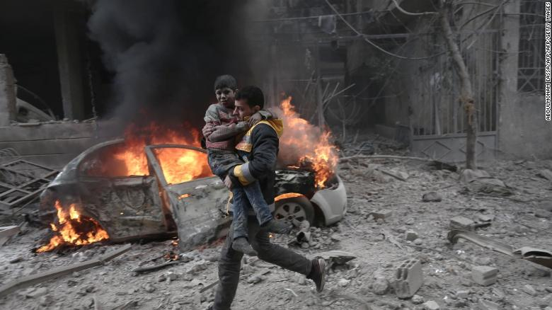 A Syrian rescuer carries an injured child following airstrikes in Eastern Ghouta on Saturday.