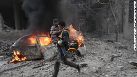 TOPSHOT - A Syrian paramedic carries an injured child following reported bombardment by Syrian and Russian forces in the rebel-held town of Hamouria, in the Eastern Ghouta, on January 6, 2018. Regime and Russian air strikes on a rebel-held enclave near the Syrian capital killed at least 17 civilians, a war monitor said. / AFP PHOTO / ABDULMONAM EASSA        (Photo credit should read ABDULMONAM EASSA/AFP/Getty Images)
