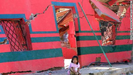 A girl sits in front of a building destroyed by the January 2001 earthquake in San Agustin, El Salvador.