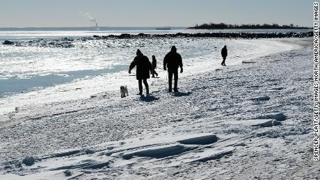 WESTPORT, CT - JANUARY 07:  People walk along a beach covered in snow and ice as temperatures continue to stay below freezing in much of the Northeast on January 7, 2018 in Westport, Connecticut. Following a heavy snowfall last Thursday, much of New England is experiencing Arctic like weather conditions with temperatures plunging well below freezing. Some relief is expected on Monday as temperatures are expected in the high 30Õs and low 40Õs.  (Photo by Spencer Platt/Getty Images)