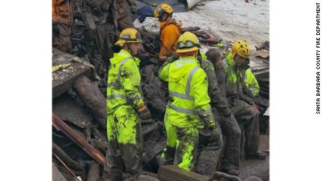 Firefighters lead a girl, 14, from the rubble where she'd been trapped for hours Tuesday in Montecito.