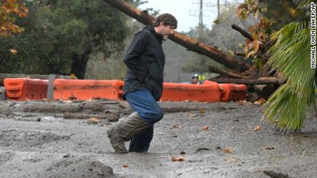 Carpinteria resident Scott Mayfield walks through the mud on Foothill Road in Carpinteria, Calif., Tuesday, Jan. 9, 2018. (AP Photo/Michael Owen Baker)