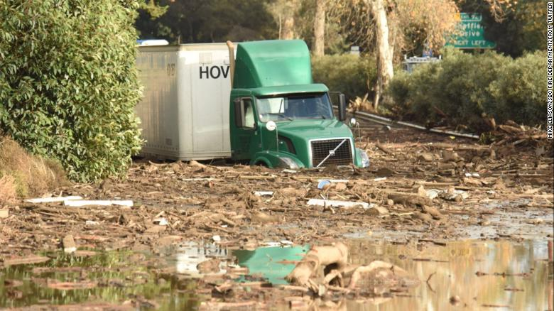 A tractor trailer in Southern California is stuck in mud and debris.