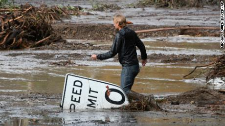 Phillip Harnsberger crosses through mud from a flooded creek on Sheffield Drive in Montecito, Calif., following heavy rain, Tuesday, Jan. 9, 2018. Multiple people were killed and homes were torn from their foundations Tuesday as downpours sent mud and boulders roaring down hills stripped of vegetation by a gigantic wildfire that raged in Southern California last month. (AP Photo/Michael Owen Baker)