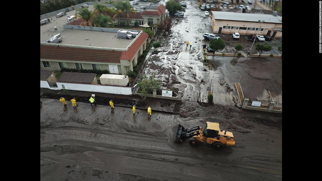 Los Angeles firefighters work amid floodwaters and mud on January 9.