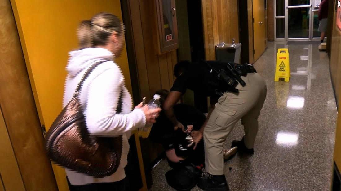 A teacher is handcuffed and jailed after criticizing school superintendent's raise a school board meeting.