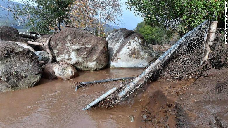 Mudslides pushed boulders near a broken fence in Carpinteria on Tuesday.