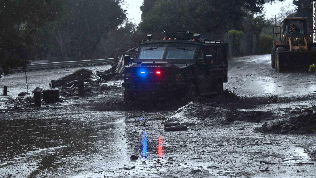 A police vehicle drives across a flooded side road in Montecito, near the San Ysidro exit of Highway 101 on January 9.