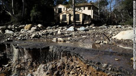 Water pours off of a road that was damaged by a mudslide on January 10, 2018 in Montecito, California. 15 people have died and hundreds are still stranded after massive mudslides crashed through Montecito, California early Tuesday morning.