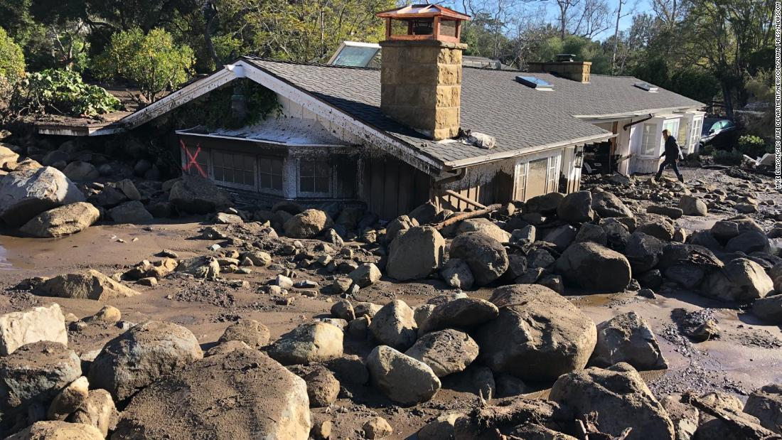 Kerry Mann navigates the large boulders and mudflow that destroyed her friend's home in Montecito.