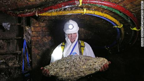 "TO GO WITH AFP STORY BY ROBIN MILLARD Tim Henderson, a ""flusher"" or trunk sewer technician holds a ""fatberg"" as he works in the intersection of the Regent Street and Victoria sewer in London on December 11, 2014. Every day beneath the streets of London, sewer cleaners are fighting a grim war against giant ""fatbergs"" clogging the system. Congealed fat is blocking up the Victorian sewers and the problem is to get worse at Christmas. An extra two Olympic-sized swimming pools of turkey fat will be tipped down the drains during the festive season. There are 80,000 fatberg blockages a year, costing Thames Water customers ?1 million ($1.6 million, 1.3 million euros) each month to tackle. The company urges people people to dispose of their cooking oil and fat properly. ""Bin it, don't block it"" is their message. AFP PHOTO / ADRIAN DENNIS        (Photo credit should read ADRIAN DENNIS/AFP/Getty Images)"