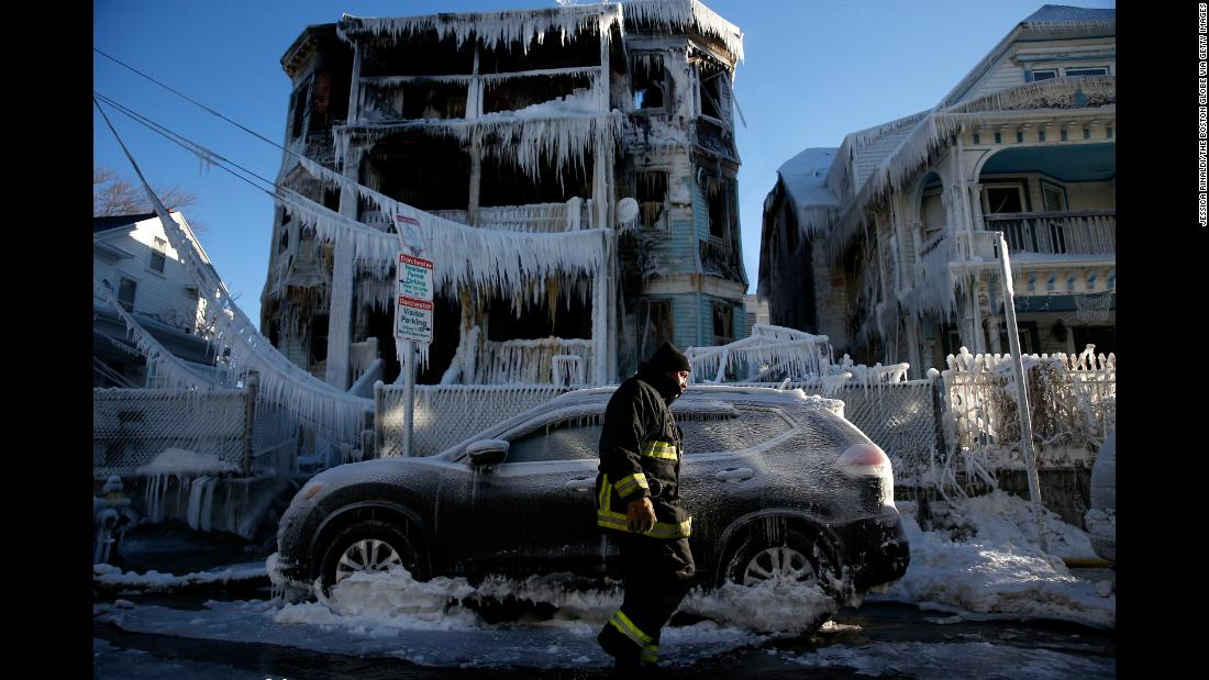 A firefighter walks past a Boston house that caught fire the night before on Saturday, January 6.