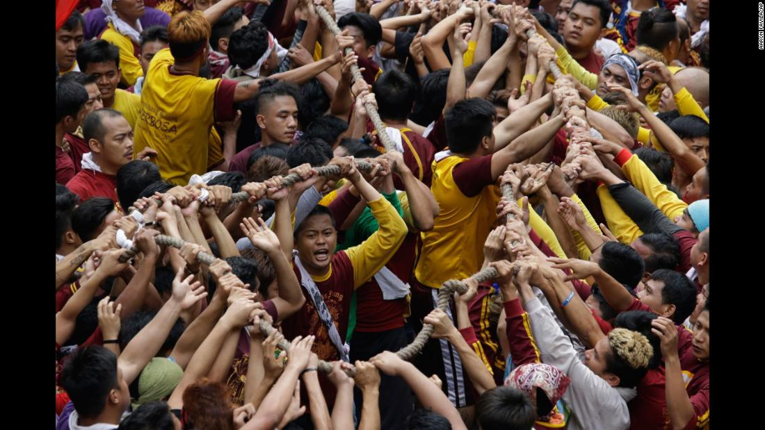 Roman Catholics grab a rope, pulling a carriage with an image of the Black Nazarene, during a procession in Manila, Philippines, on Tuesday, January 9.