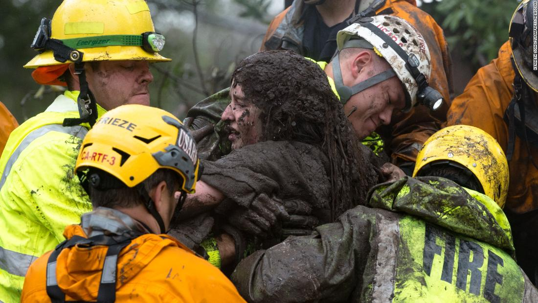 "Emergency personnel carry a woman from a collapsed house after a mudslide in Montecito, California, on Tuesday, January 9. <a href=""http://www.cnn.com/2018/01/09/us/gallery/southern-california-mudslides-flooding/index.html"" target=""_blank"">See more photos from the mudslides</a>"