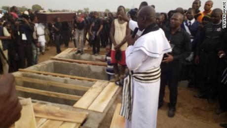 Priest administers burial rites at the mass burial