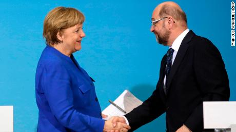 Merkel (L) shakes hands with Martin Schulz during a joint statement after talks on Friday.