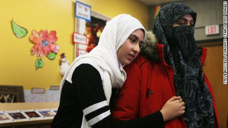 Khawlah Noman, 11, hugs her mother,  Saina Samad, after talking to reporters Friday in Toronto.