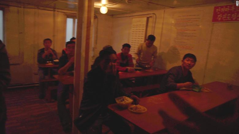 North Korean workers eat lunch in their canteen.