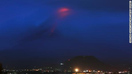 The glow (at top) of lava from the cloud-covered Mayon volcano as it erupts is pictured from the Philippine city of Legazpi in Albay province, early on January 15, 2018. The Philippines raised the alert level for the country's most active volcano twice in 24 hours on January 14, meaning that a hazardous eruption is possible within days. / AFP PHOTO / Simvale SAYAT        (Photo credit should read SIMVALE SAYAT/AFP/Getty Images)