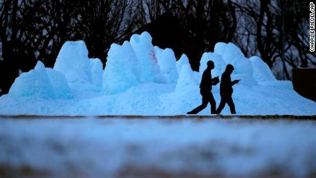 People walk past a frozen fountain Monday, Jan. 15, 2018, at a park in Kansas City, Mo. The latest round of sub-zero weather to hit the region has prompted some schools to cancel classes Tuesday. (AP Photo/Charlie Riedel)