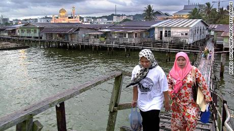 Two women make their way home through Kampong Ayer water village at dusk as the Sultan Omar 'Ali Saifuddien mosque (back-L) is illuminated, in the city of Bandar Seri Begawan, 14 November 2000, the scene of this week's Asia Pacific Economic Cooperation (APEC) forum.  World leaders from the Asia-Pacific region's flagship 21-member economic forum are meeting in the conservative Islamic sultanate of Brunei 15-16 November.     AFP PHOTO/Romy GACAD        (Photo credit should read ROMEO GACAD/AFP/Getty Images)