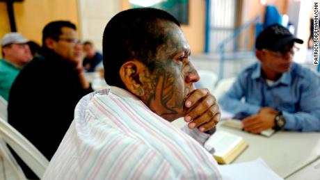 An ex-member of the Barrio 18 gang listens to a church sermon. Salvadoran gang members often cover themselves in tattoos to show their unwavering allegiance to the gangs. The tattoos make leaving gang life even harder.