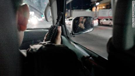 While on patrol, a member El Salvador's National Civil Police points his assault rifle out the car window. Police say gang members often possess more fire power than they do.