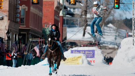 Rider Savannah McCarthy races down Harrison Avenue while skier Mike Fries airs out off the final jump of the Leadville skijoring course during the 68th annual Leadville Ski Joring weekend competition on Saturday, March 4, 2017 in Leadville, Colorado. S Skijoring, which has its origins as a competitive sport in Scandinavia, has been adapted over the years to include a team made up of a rider and skier who must navigate jumps, slalom gates, and the spearing of rings for points. Leadville, with an elevation of 10,152 feet (3,094 m), the highest incorporated city in North America, has been hosting skijoring competitions since 1949. / AFP PHOTO / Jason Connolly        (Photo credit should read JASON CONNOLLY/AFP/Getty Images)