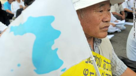 "A South Korean liberal activist waves the ""reunification flag"" painted the Korean Peninsula during a rally to welcome Reverend Han Sang-Ryol, at the Imjingang railway station near a military-controlled bridge leading to Panmunjom in Paju, north of Seoul, on August 20, 2010.  A South Korean pro-unification activist was arrested when he crossed the tense border from North Korea after visiting Pyongyang without Seoul's permission.  AFP PHOTO/PARK JI-HWAN (Photo credit should read PARK JI-HWAN/AFP/Getty Images)"
