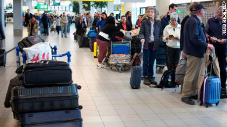 A group of travelers line up at Schiphol Airport near Amsterdam, Thursday.