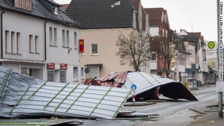 "A picture taken on January 18, 2018 shows metal roofing sheets from a supermarket blocking a road in Menden, western Germany, as the region is hit by the storm named ""Friederike""."