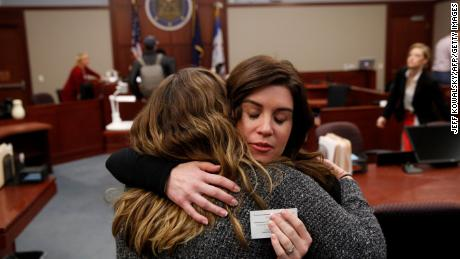Larissa Boyce (R) gets a hug from Alexis Alvarado, both victims of Larry Nassar, during a hearing in Ingham County Circuit Court on November 22, 2017 in Lansing, Michigan. Former USA Gymnastics team doctor Lawrence (Larry) Nassar, accused of molesting dozens of female athletes over several decades, on Wednesday pleaded guilty to multiple counts of criminal sexual conduct. Nassar -- who was involved with USA Gymnastics for nearly three decades and worked with the country's gymnasts at four separate Olympic Games -- could face at least 25 years in prison on the charges brought in Michigan.  / AFP PHOTO / JEFF KOWALSKY        (Photo credit should read JEFF KOWALSKY/AFP/Getty Images)