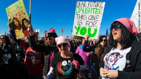 "LAS VEGAS, NV - JANUARY 21:  Protesters carry signs as they make their way to Sam Boyd Stadium for the Women's March ""Power to the Polls"" voter registration tour launch on January 21, 2018, in Las Vegas, Nevada. Demonstrators across the nation gathered over the weekend, one year after the historic Women's March on Washington, D.C., to protest President Donald Trump's administration and to raise awareness for women's issues.  (Photo by Sam Morris/Getty Images)"